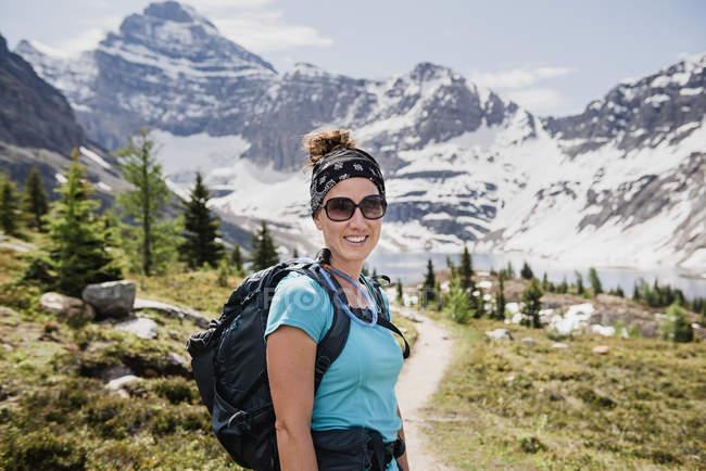 Randonneur féminin confiant de portrait sur le sentier ensoleillé et idyllique de montagne, parc de Yoho, Colombie-Britannique, Canada — Photo de stock