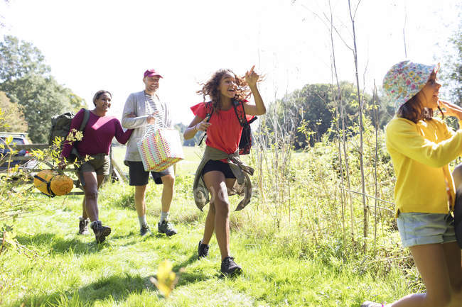 Eager family carrying camping equipment in sunny field — Stock Photo