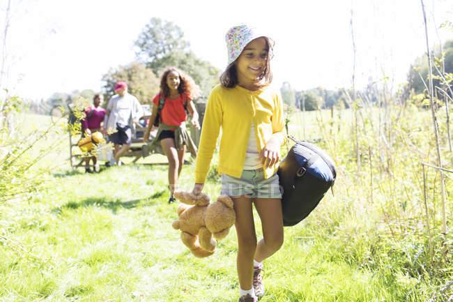 Mädchen zeltet mit Familie, trägt Schlafsack und Teddybär — Stockfoto