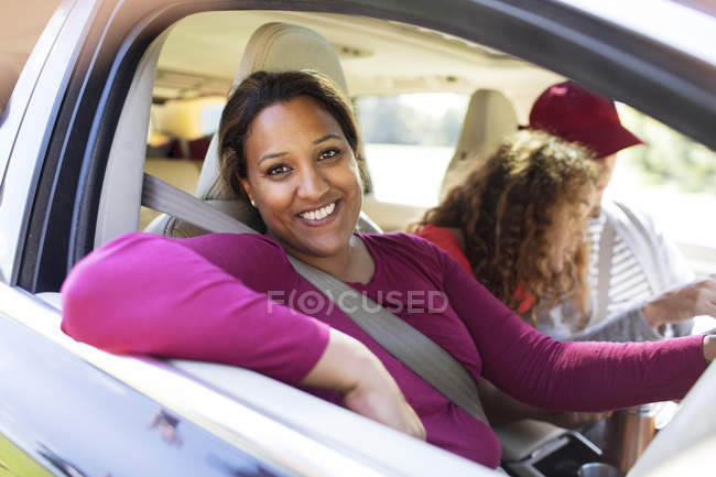 Portrait happy woman in car with family on road trip — Stock Photo