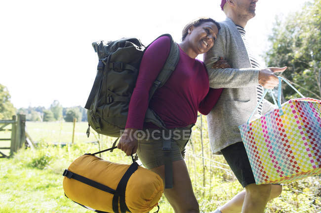 Affectionate couple carrying camping equipment — Stock Photo