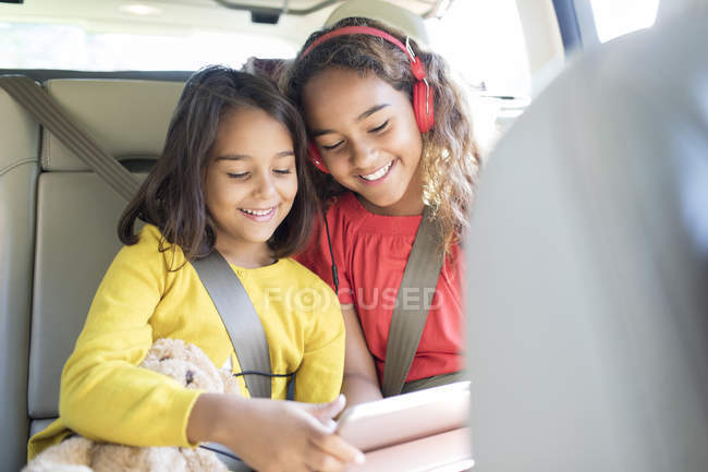 Sisters using digital tablet in back set of car — Stock Photo