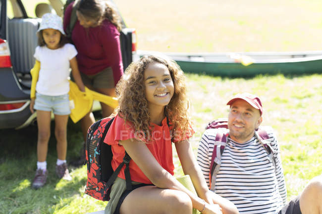 Portrait happy girl camping with family, unloading car in sunny field — Stock Photo