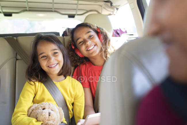 Happy sisters riding in back seat of car — Stock Photo