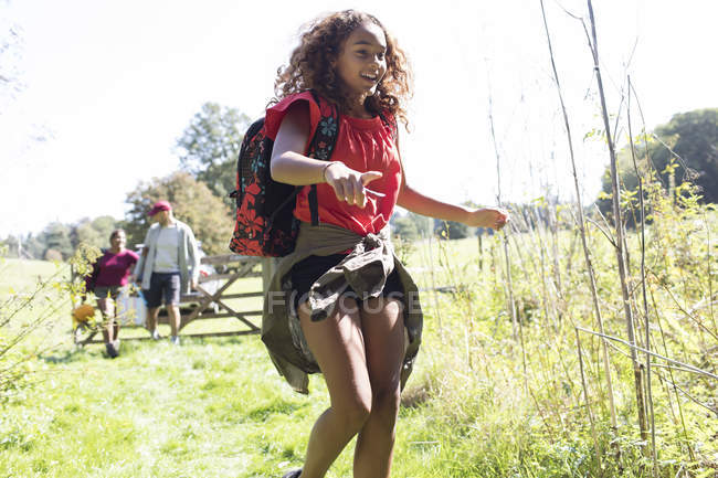 Happy girl with backpack camping, running in sunny field — стокове фото