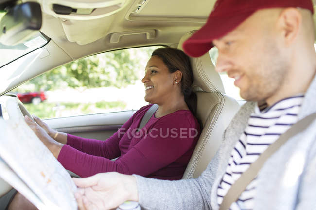 Couple with map driving in car on road trip — Stock Photo