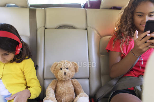 Sisters with teddy bear using smart phone and digital tablet, riding in back seat of car — Stock Photo