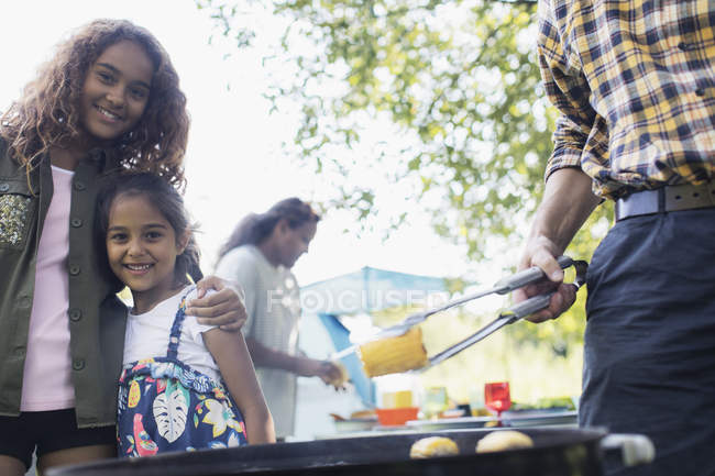 Portrait happy sisters enjoying backyard barbecue — Stock Photo