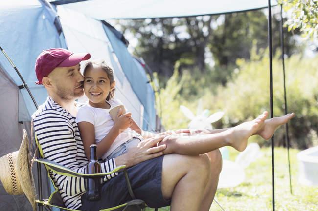 Счастливый, любящий отец держит дочь на коленях в солнечном лагере — стоковое фото
