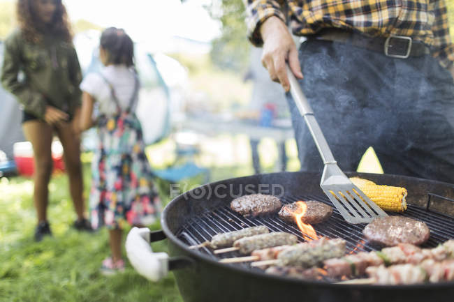 Homme barbecue hamburgers, kebabs et épis de maïs — Photo de stock