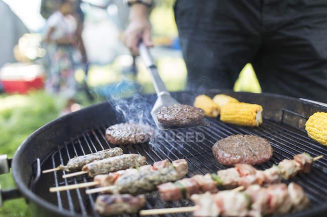 Man barbecuing hamburgers, kebabs and corn cobs — Stock Photo