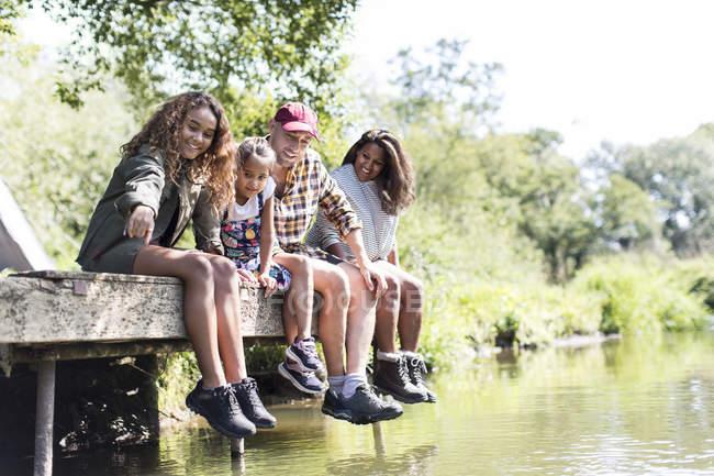 Семья сидит на солнечном причале у реки — стоковое фото