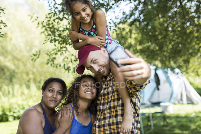 Selfie teniendo familia feliz, afectuoso con la cámara del teléfono en el camping - foto de stock