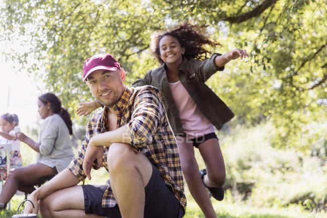Счастливая дочь бежит обнимать отца в кемпинге — стоковое фото