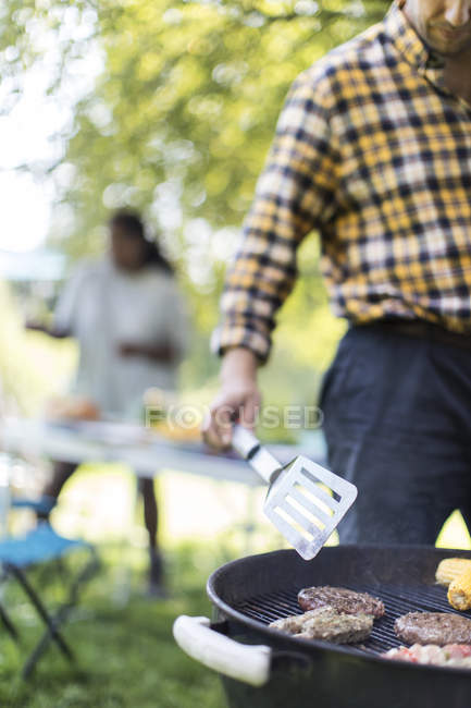 Man barbecuing hamburgers on grill — Stock Photo