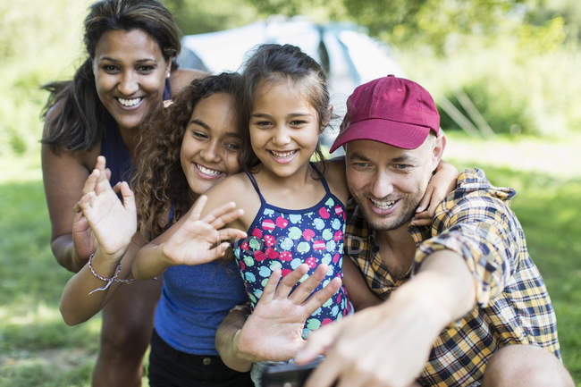 Happy family waving, taking selfie with camera phone at campsite — Stock Photo