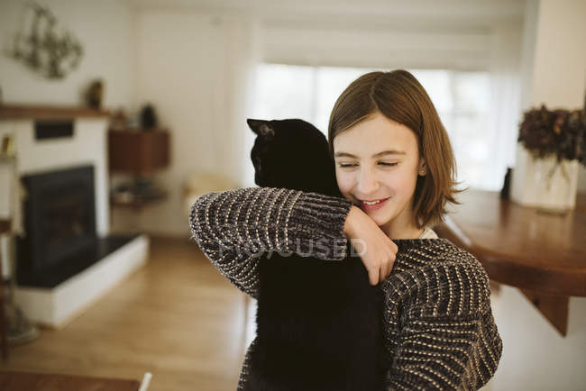 Affectionate girl holding black cat — Stock Photo