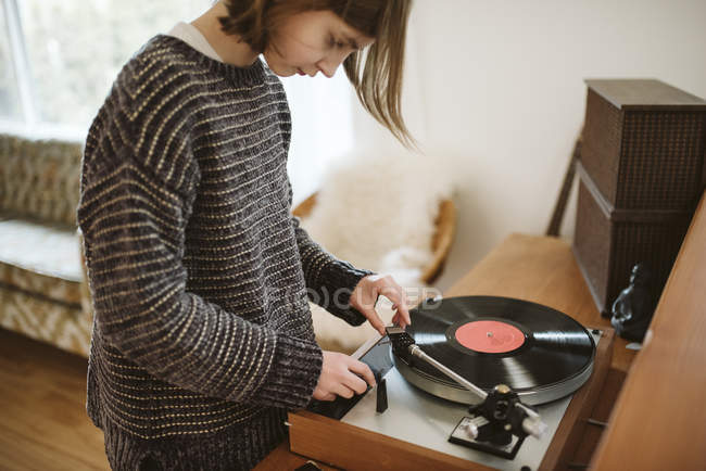 Girl playing vinyl record in living room — Stock Photo