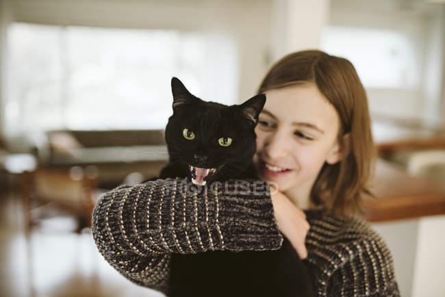 Портрет дівчина Холдинг шипіння чорний кіт — стокове фото