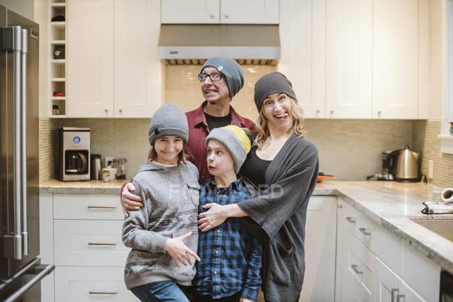 Família parva do retrato que faz as faces na cozinha — Fotografia de Stock