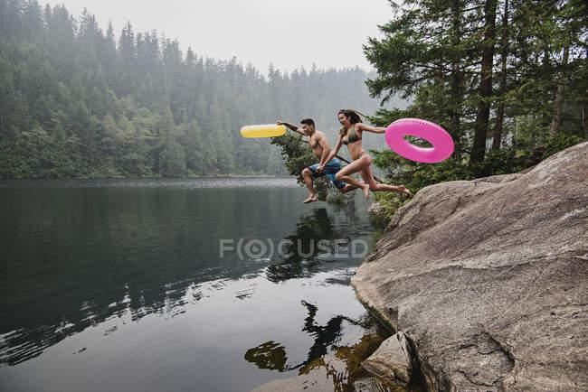 Giocoso giovane coppia con anelli gonfiabili saltare in lago remoto, Squamish, British Columbia, Canada — Foto stock
