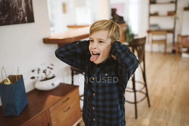 Playful, silly boy sticking out tongue and covering ears — Stock Photo