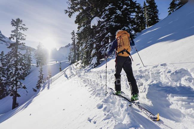 Лыжник, двигаясь по солнечной заснеженной трассе на солнечном идиллическом склоне горы — стоковое фото