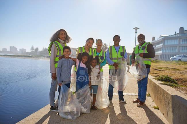 Портрет счастливые добровольцы собирают мусор на солнечной набережной — стоковое фото