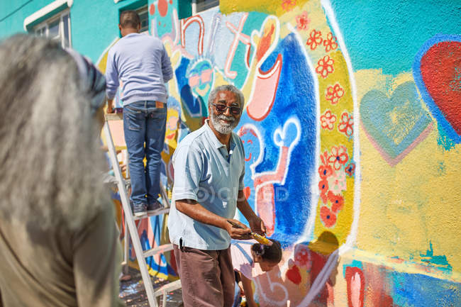 Senior man volunteer painting vibrant mural on sunny wall — Stock Photo