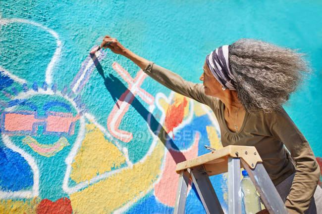 Senior woman painting vibrant mural on sunny wall — Stock Photo
