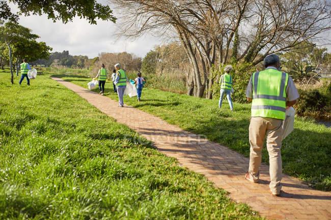 Добровольцы убирают мусор в солнечном парке — стоковое фото