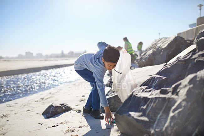 Мальчик-волонтер собирает мусор на солнечном пляже — стоковое фото