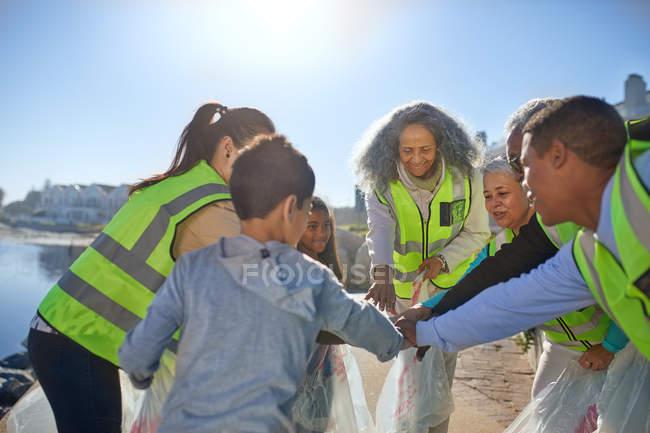 Voluntários que formam o Huddle, limpando a maca na praia ensolarada — Fotografia de Stock