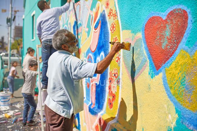 Senior man painting mural on sunny urban wall — Stock Photo