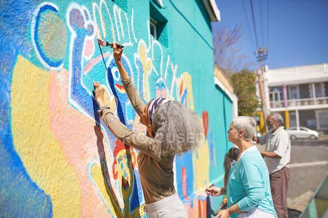 Senior community volunteers painting vibrant mural on sunny urban wall — Stock Photo