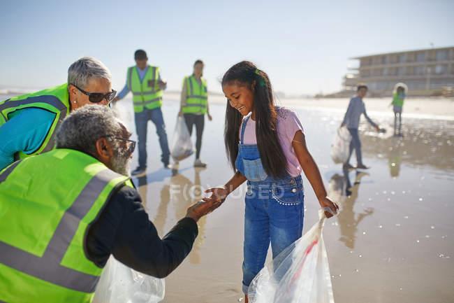 Бабушка и внучка-волонтеры убирают мусор на солнечном песчаном пляже — стоковое фото