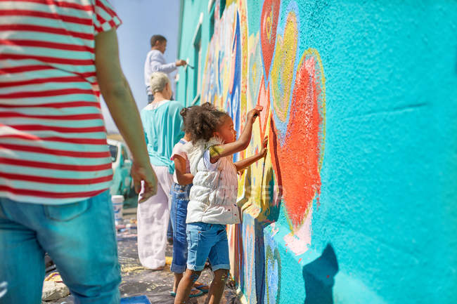 Girl volunteer painting vibrant mural on sunny wall — Stock Photo