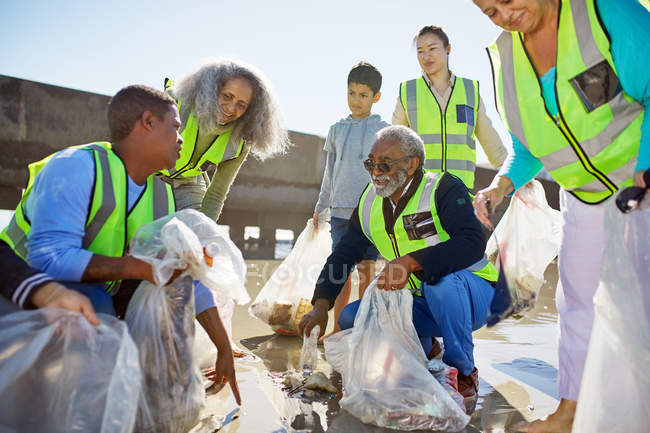Des bénévoles nettoient la litière sur une plage ensoleillée — Photo de stock