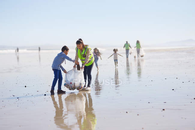 Mother and son volunteers cleaning litter on sunny, wet sand beach — Stock Photo