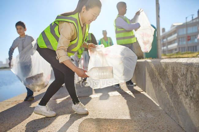 Женщина-волонтер собирает пластиковый мусор на солнечной набережной — стоковое фото