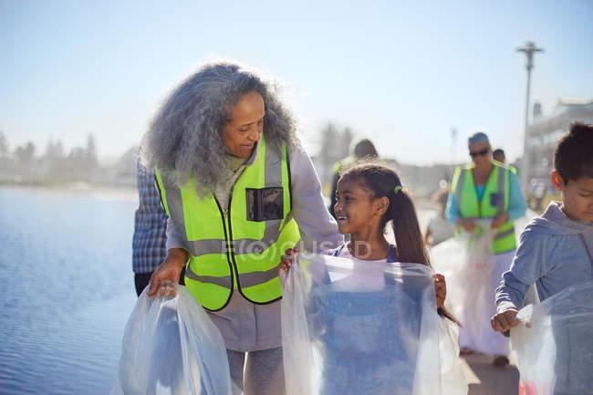 Des bénévoles de grand-mère et petite-fille ramassent la litière sur la promenade — Photo de stock