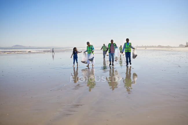 Volunteers cleaning up litter on sunny wet sand beach — Stock Photo