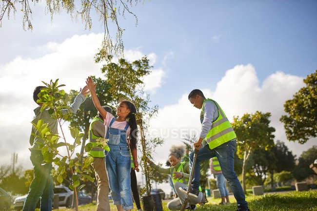Volontaires enfants haut de cinq ans, plantation d'arbres dans un parc ensoleillé — Photo de stock