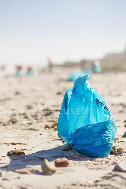 Sac poubelle de nettoyage bleu sur une plage de sable ensoleillée — Photo de stock