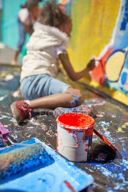 Girl painting mural behind paint can — Stock Photo