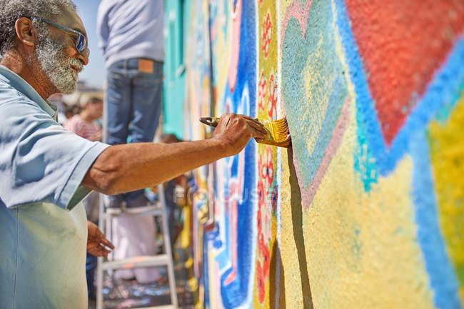 Senior man painting mural on sunny wall — Stock Photo