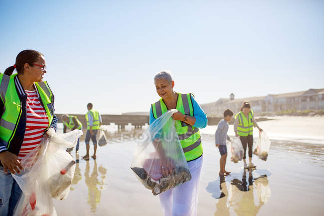 Volunteers cleaning up litter on sunny, wet sand beach — Stock Photo