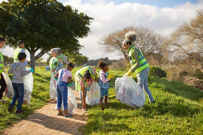Des bénévoles nettoient la litière dans un parc ensoleillé — Photo de stock