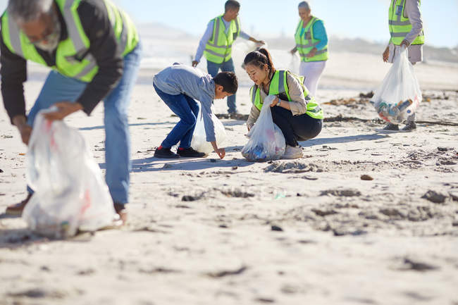 Mother and son volunteers cleaning up litter on sunny, sandy beach — Stock Photo