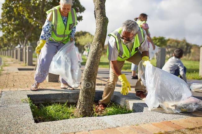 Des bénévoles âgés nettoient la litière dans un parc ensoleillé — Photo de stock